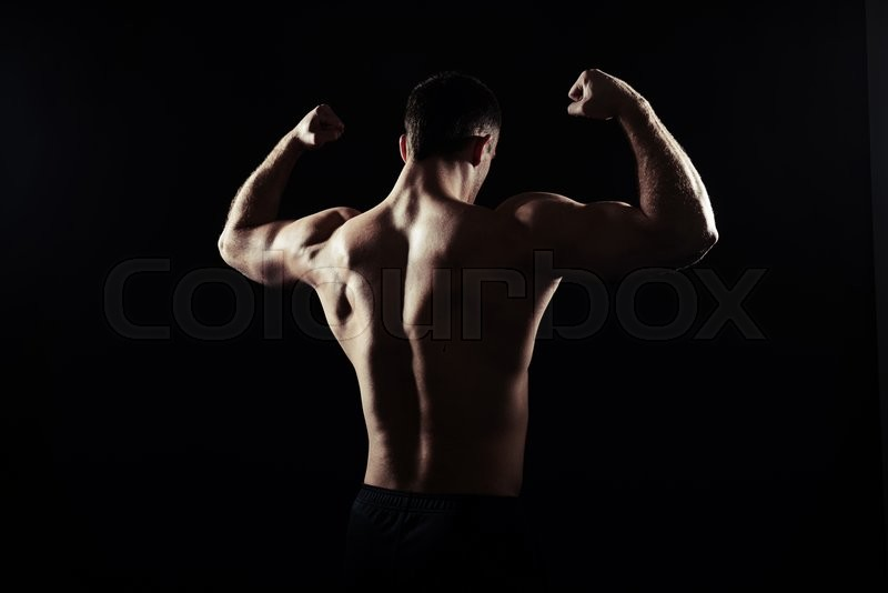 Stock image of 'Back view silhouette of hot shirtless athletic guy showing muscles over black background'