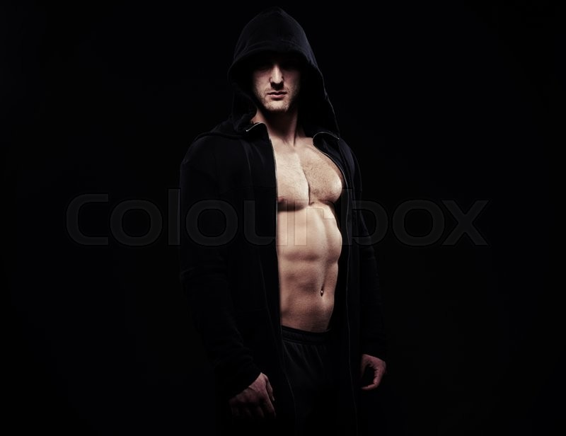 Stock image of 'Portrait of athletic bare-chested guy in dark sport jacket with hood showing his well trained muscular body with abs and biceps over black background'