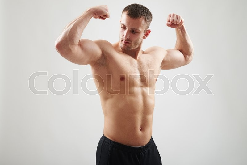 Stock image of 'Young fit muscular bare-chested man is showing muscles isolated on white background'