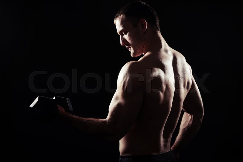 Stock image of 'Bare-chested sexy muscular man is standing over black background with dumbbell in his hand, view from the back'