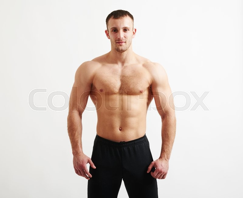 Stock image of 'Bare-chested young athletic man in black pants is standing isolated over white background'