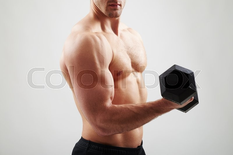 Stock image of 'Close-up of bare-chested athletic guy who is holding a dumbbell in his hand and showing muscles on white background'