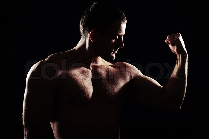 Stock image of 'Close-up silhouette of hot muscular bare-chested guy showing biceps isolated over black background'