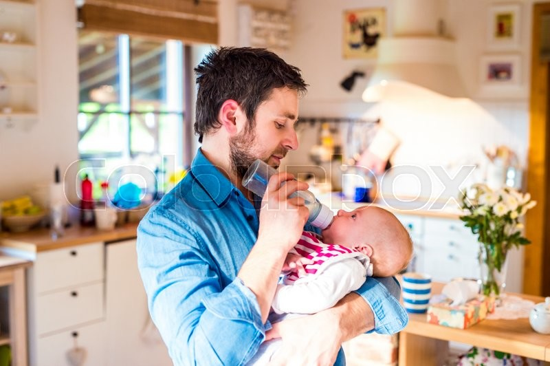 Stock image of 'Young father feeding his cute newborn baby son, holding him in his arms'