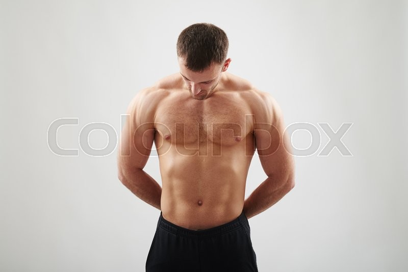 Stock image of 'Handsome young athletic muscular man with bare chest is standing isolated over white background and looking down'