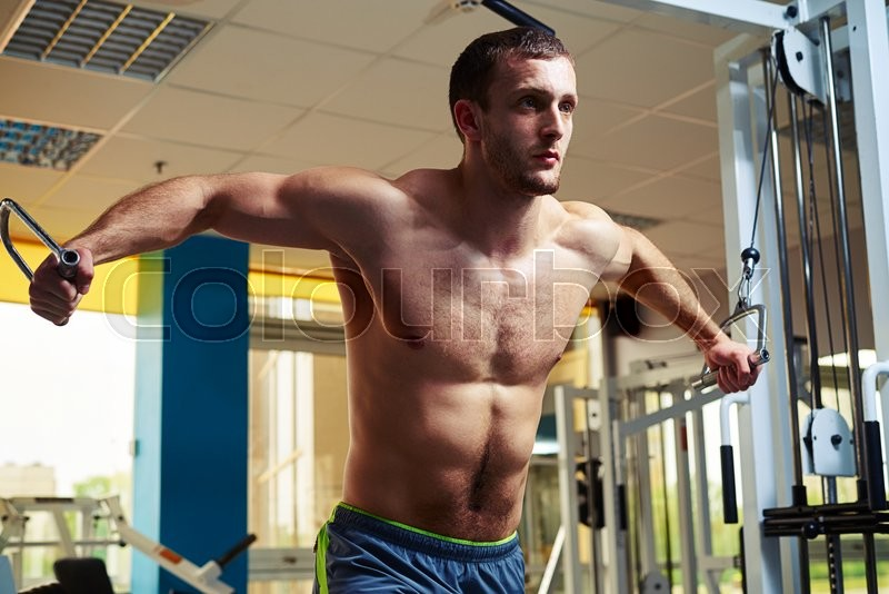 Stock image of 'Young strong man with torso is doing flys on cable crossover in gym'