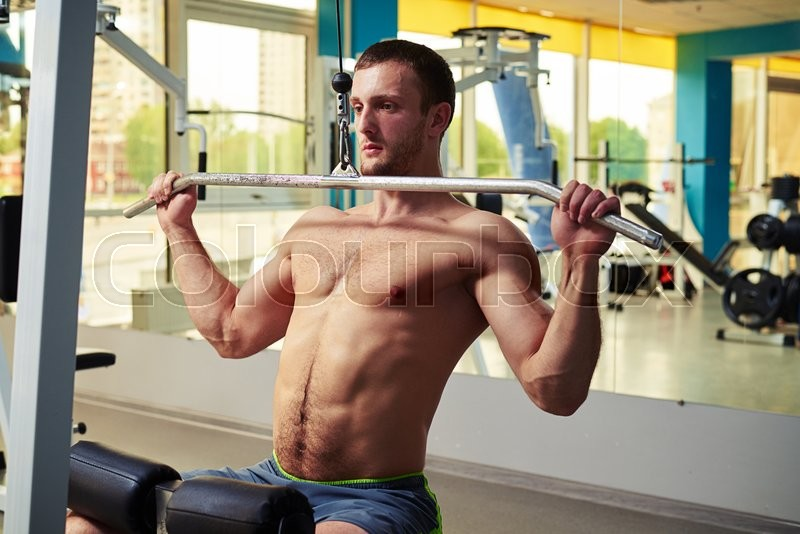 Stock image of 'A fit young man in blue shorts is doing shoulder exercises on cable machine in gym'