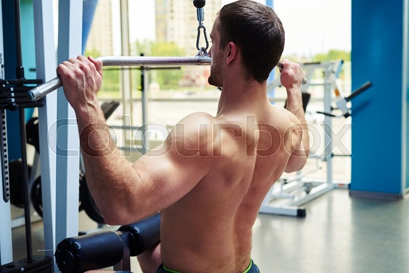 Stock image of 'Close-up of a fit young man who is doing shoulders workout on the machine in gym'
