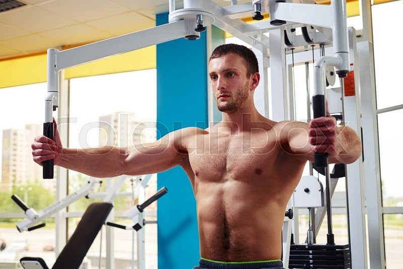 Stock image of 'Strong young man is working out his chest muscles on the machine in gym'