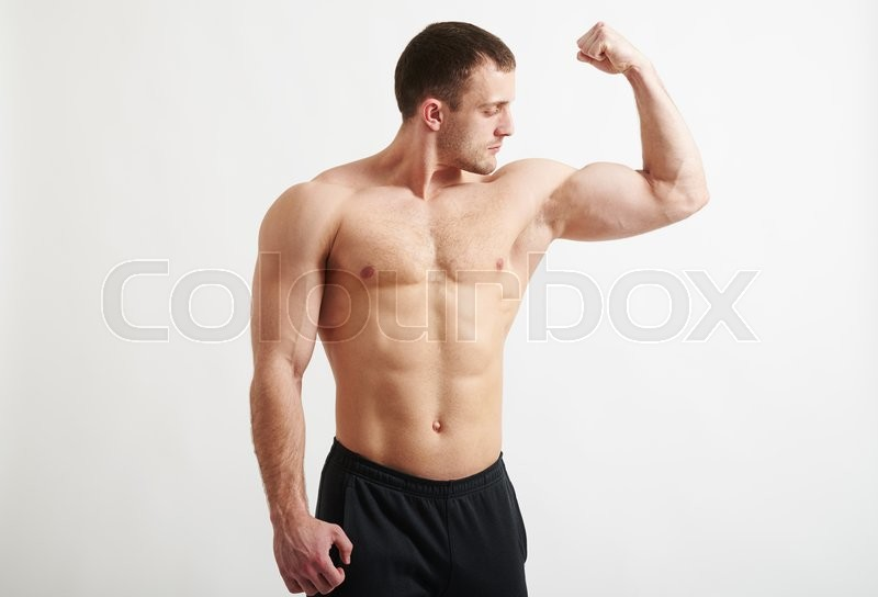 Stock image of 'Young fit muscular man is showing his biceps isolated on white background'