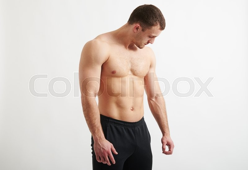 Stock image of 'Bare-chested healthy handsome muscular man in black pants is standing over white background and looking down at his hand'
