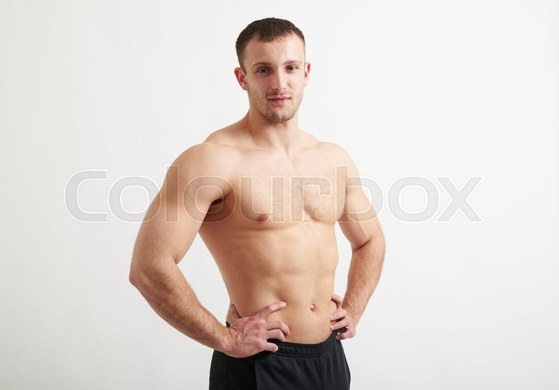 Stock image of 'Healthy bare-chested handsome muscular man in black pants is standing over white background holding hands on his hips'