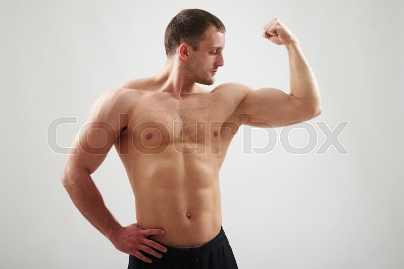 Stock image of 'Sexy athletic bare-chested man in black pants is showing biceps on his left arm isolated on white background'