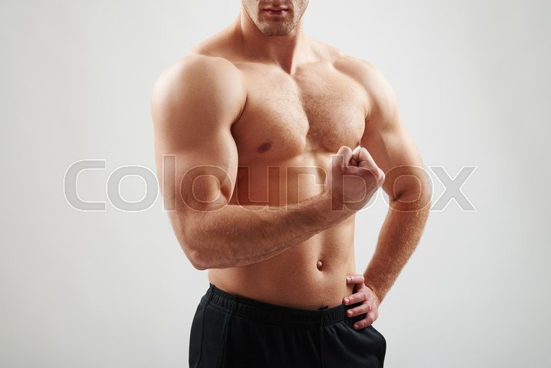 Stock image of 'Close-up of sexy athletic muscular guy with bare torso who is flexing biceps on white background'