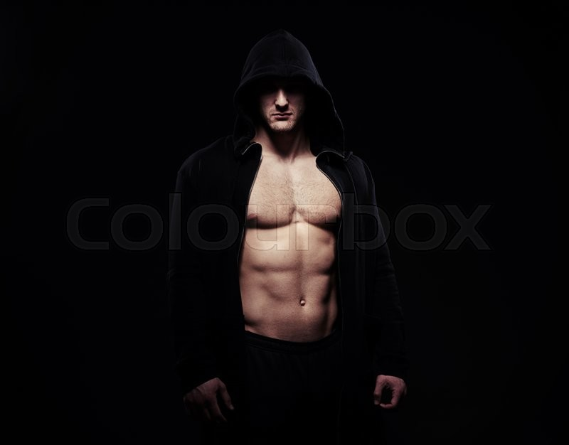 Stock image of 'Silhouette of hot muscular young man in dark sport jacket over black background with naked torso, his eyes hidden by the hood'