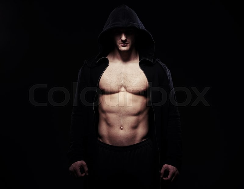 Stock image of 'Silhouette of sexy athletic guy in dark sport jacket over black background with bare torso, his eyes hidden by the hood'