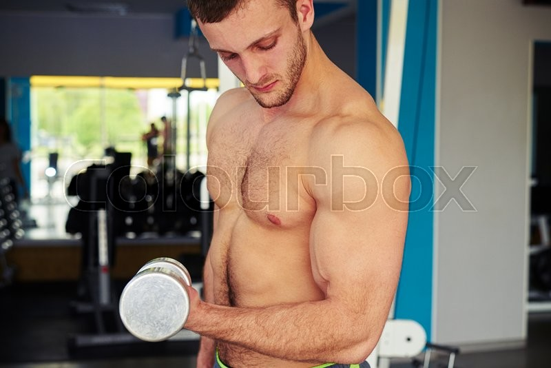 Stock image of 'Young strong guy with bare chest is holding dumbbell and flexing biceps in the gym'