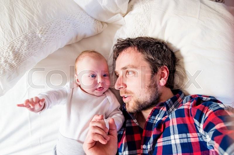 Stock image of 'Cute newborn baby boy lying on a bed, next to his father'