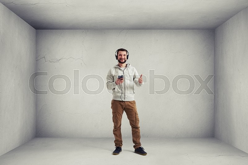 Stock image of 'Smiling Caucasian bearded man in casual clothes and headphones is standing in empty white room and showing a thumb up gesture'
