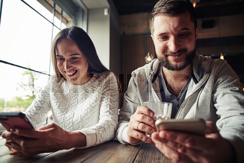 Stock image of 'A happy smiling woman and a handsome bearded man are sitting nearby each other in the cafe and looking something up in their mobile phones'