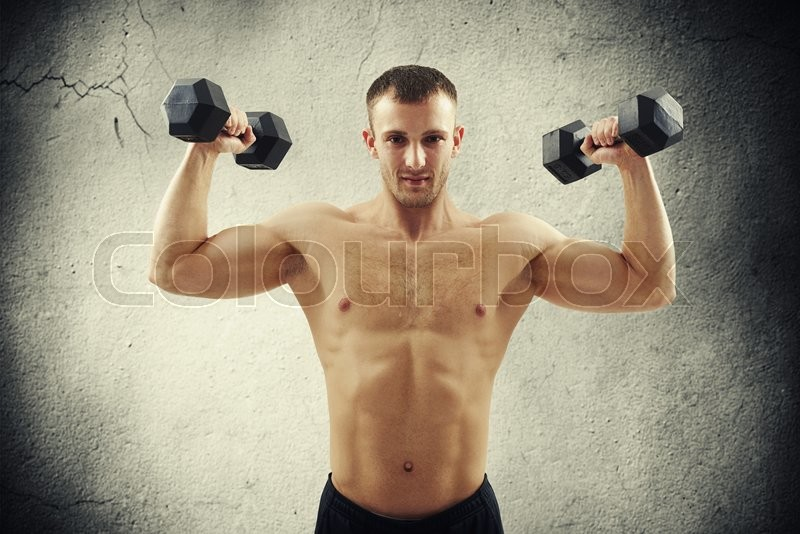 Stock image of 'Handsome young athletic muscular bare-chested man is standing isolated over concrete wall and lifting dumbbells'