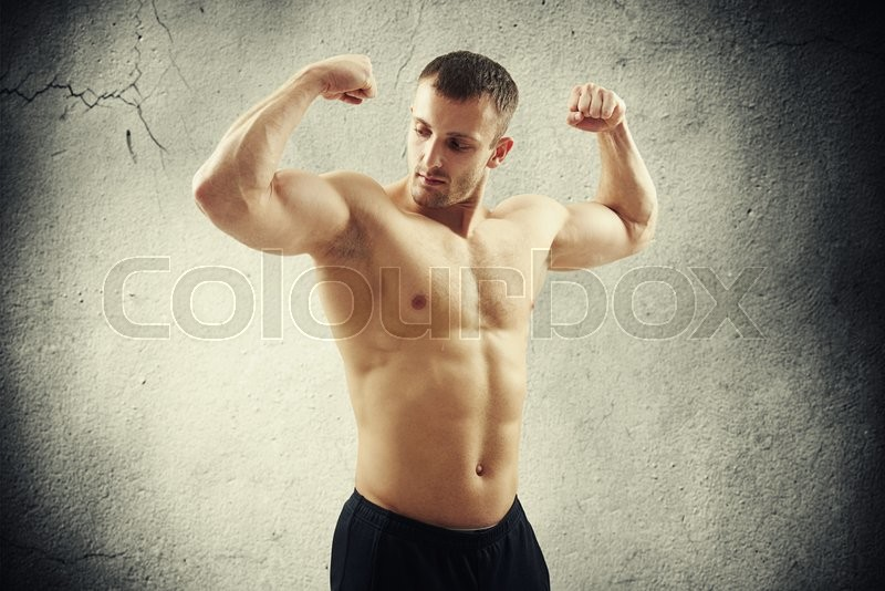 Stock image of 'Handsome young athletic muscular bare-chested man is standing isolated over concrete wall and showing biceps on both arms'