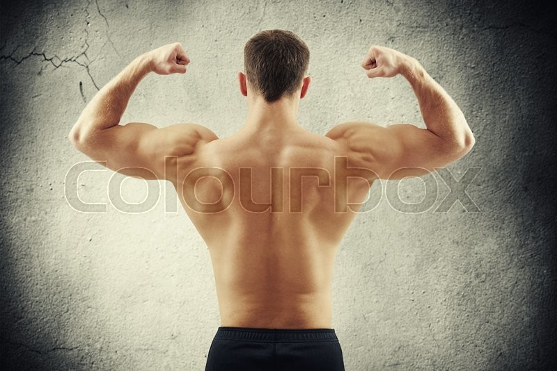 Stock image of 'Back of sexy young athletic man who is showing muscles isolated on old cracked concrete wall background'