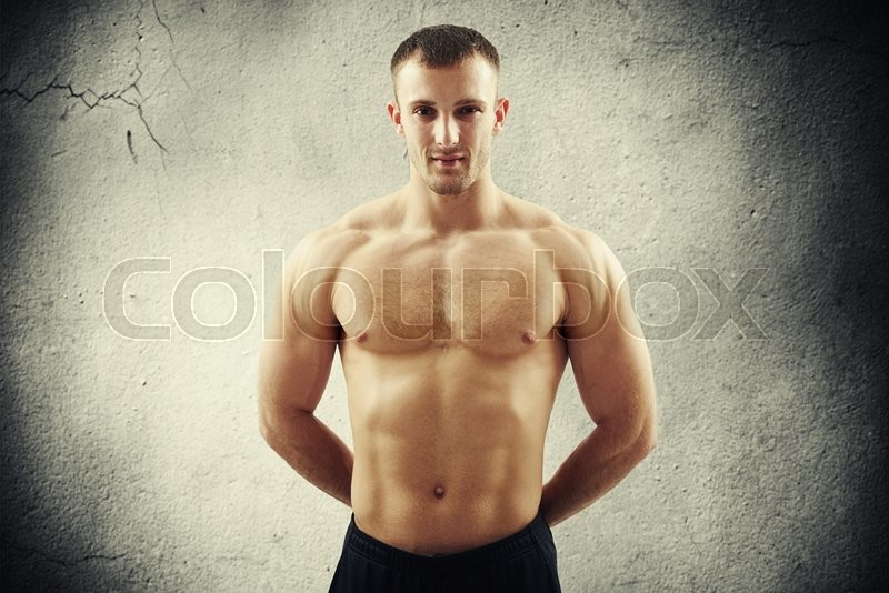 Stock image of 'Young muscular bare-chested man is standing with hands behind his back over concrete wall background'