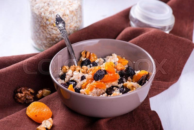 Stock image of 'Oatmeal with raisins, dried apricots, plums'