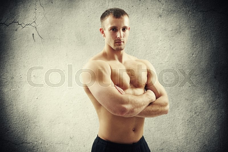 Stock image of 'Sexy athletic guy is standing bare-chested with his arms crossed isolated over concrete wall background'