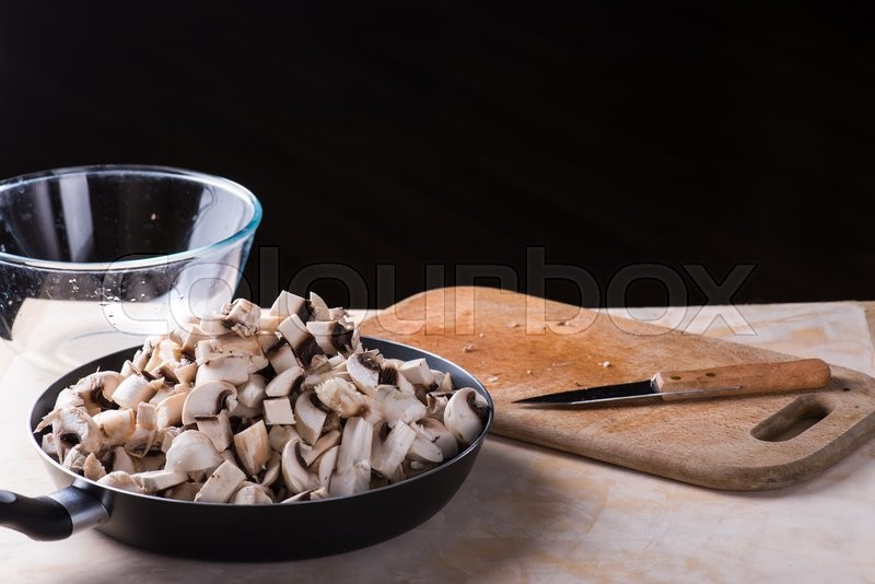 Stock image of 'fresh mushrooms cut on the wooden desk'