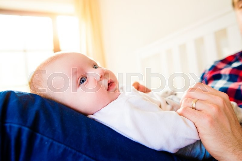 Stock image of 'Cute newborn baby boy held by his father sitting on bed'