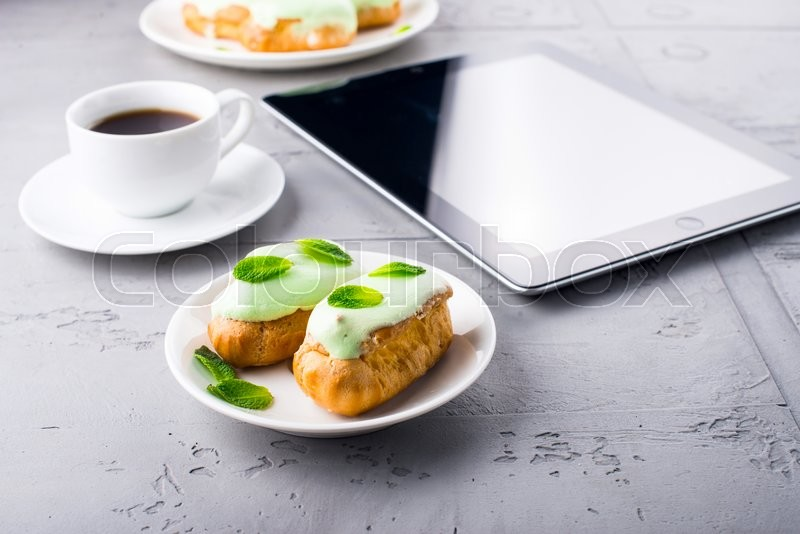 Stock image of 'Mint eclairs on a plate, cup of coffee and digital tablet'