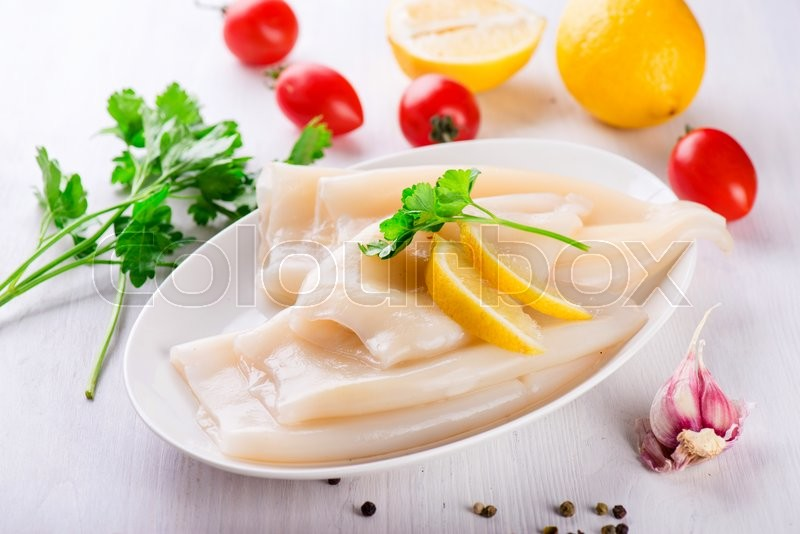 Stock image of 'Raw squid and ingredients on the white plate'