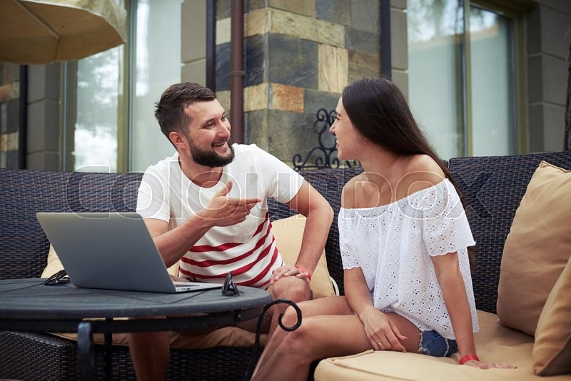 Stock image of 'Beautiful woman and young bearded man are sitting on open terrace in the yard and vividly discussing something near laptop'