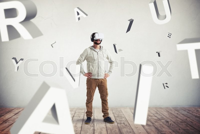 Stock image of 'Smiling Caucasian bearded man in casual clothes and headphones is wearing virtual reality glasses and standing surrounded by flying letters in empty room with white wall and wooden floor'
