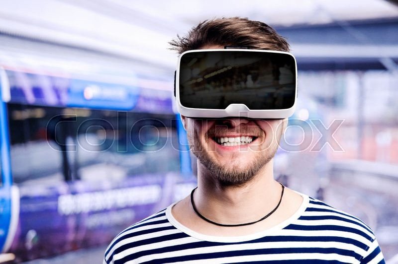 Stock image of 'Hipster man in striped black and white sweatshirt wearing virtual reality goggles, standing at train station.'