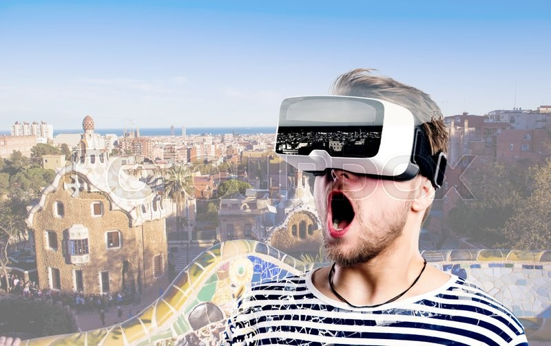 Stock image of 'Hipster man in striped black and white sweatshirt wearing virtual reality goggles. Park Guell, Barcelona, Spain.'
