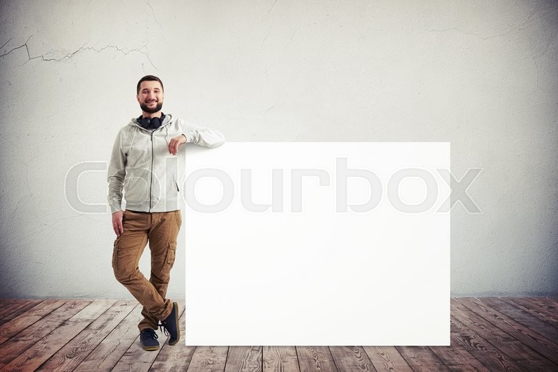 Stock image of 'Caucasian bearded man in casual clothes is standing with his elbow resting on a big white poster in white room with wooden floor'