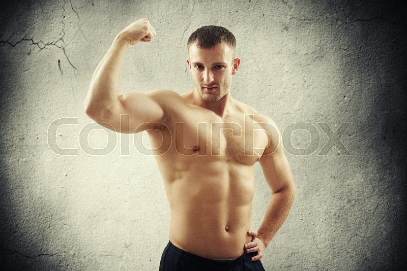 Stock image of 'Young athletic bare-chested man in black pants is showing biceps on his right arm isolated on cracked concrete wall background'