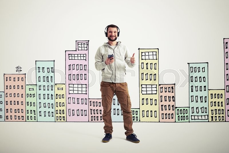 Stock image of 'Young bearded Caucasian man in casual clothes with headphones and phone is showing a thumb up gesture on white background with colorful buildings drawn on it'