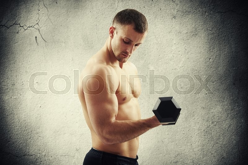 Stock image of 'Young muscular man with dumbbell is flexing biceps over old cracked concrete wall'