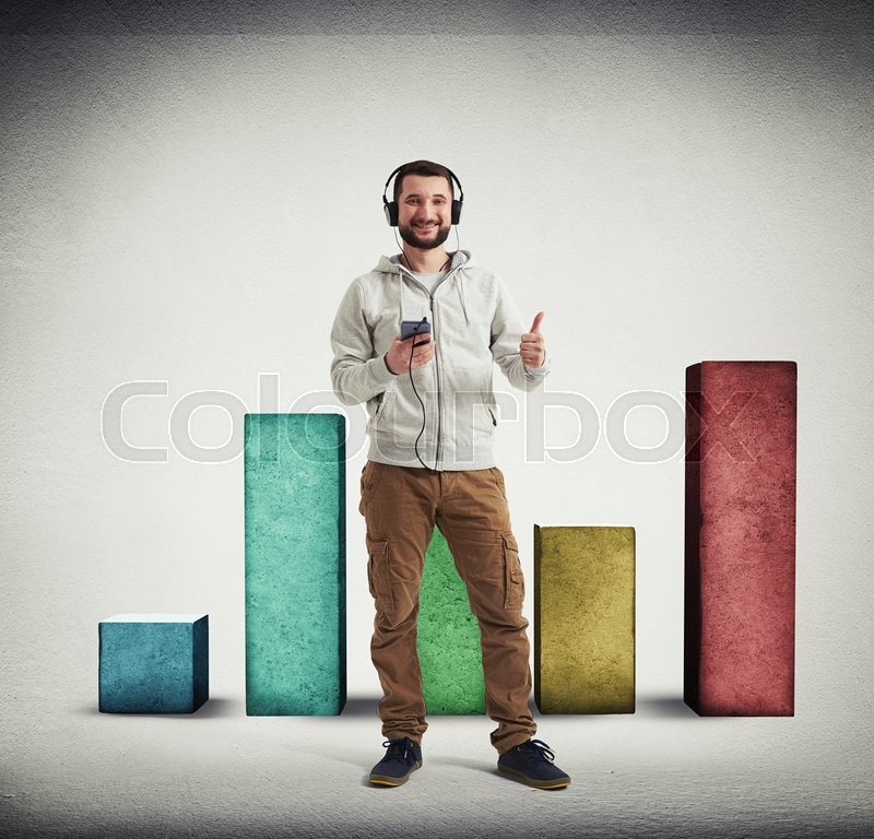 Stock image of 'Man in casual clothes and headphones is showing a thumb up gesture with big square colorful columns of different height standing behind him on white background with vignette'
