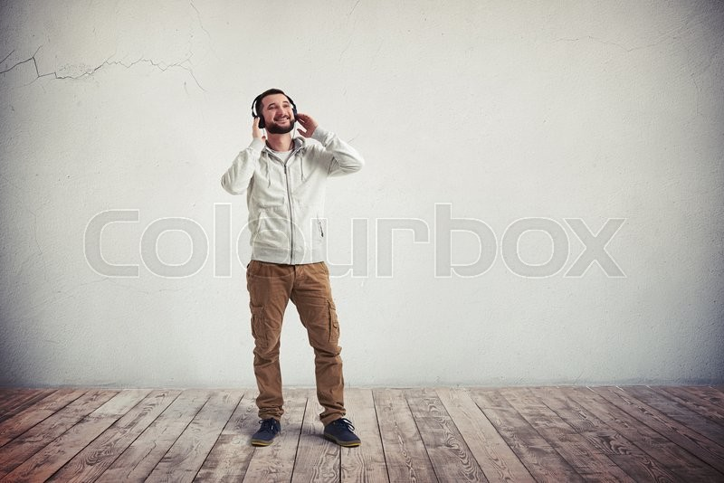 Stock image of 'Smiling young Caucasian bearded man in casual clothes and headphones is standing in empty room with white wall and wooden floor'