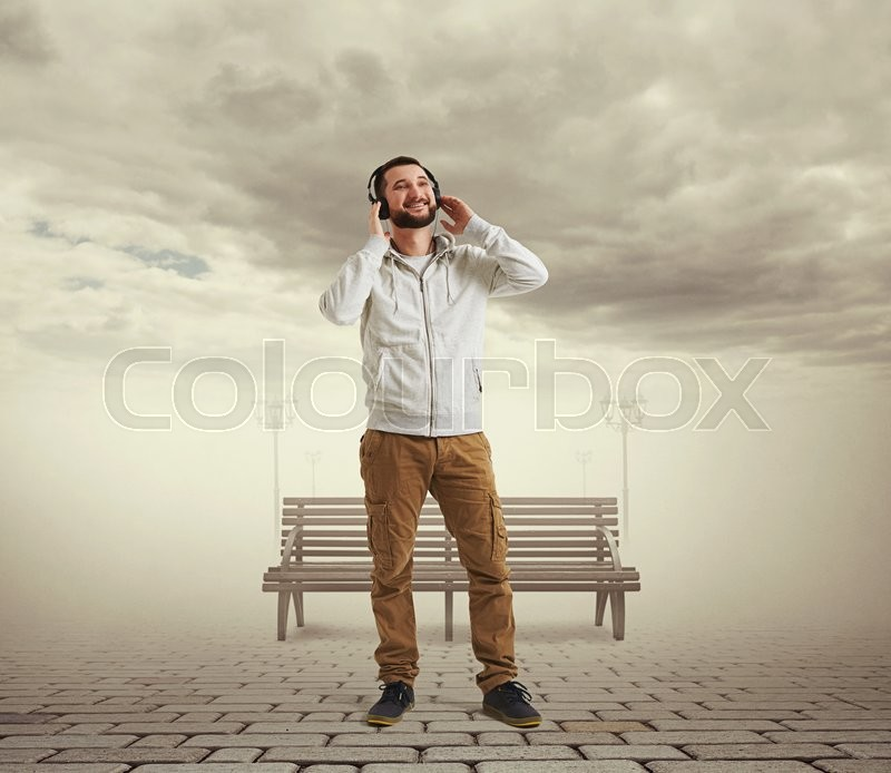 Stock image of 'Smiling young Caucasian bearded man in casual clothes and headphones is standing in virtual reality visualization of cloudy sky and lonely street with paving, street lamps and bench'