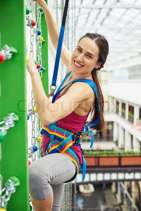 Stock image of 'Sportswoman in safety equipment is smiling while climbing on the wall with chains in indoor rock-climbing center'