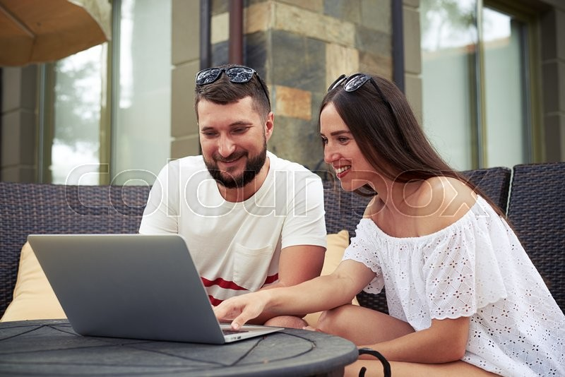 Stock image of 'Smiling beautiful woman and young bearded man are sitting with laptop on open terrace in the yard, scrolling something in laptop computer'