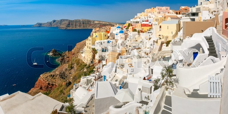 Stock image of 'Picturesque panorama of Oia or Ia on the island Santorini, white houses, windmills and church with blue domes, and island Therasia, Greece'