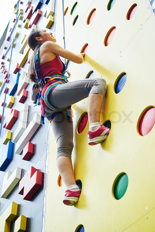 Stock image of 'A young woman in safety harness is looking upwards while climbing on the artificial rock-climbing wall'