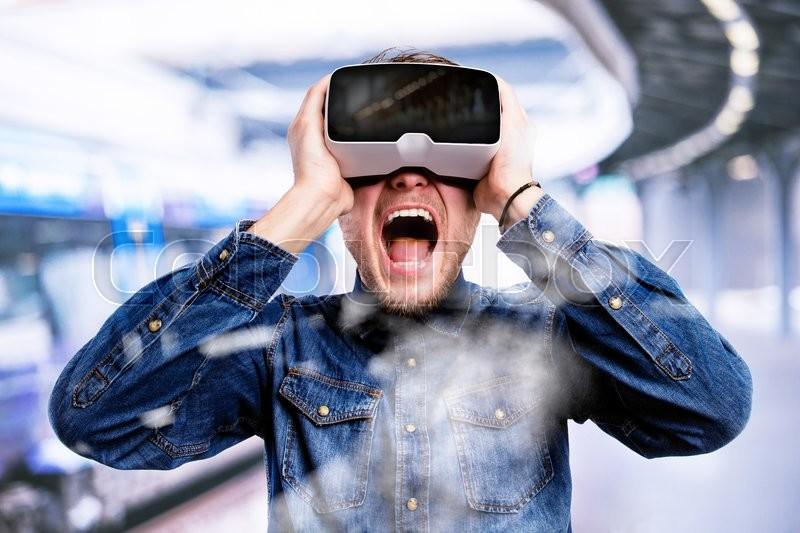Stock image of 'Hipster man in denim shirt wearing virtual reality goggles, standing at train station.'